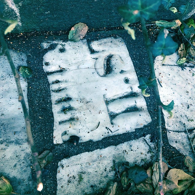 A piece of grave marker embedded in a wall in Buena Vista Park - there are some letters of the gravestone engraving still visible, but it's unreadable