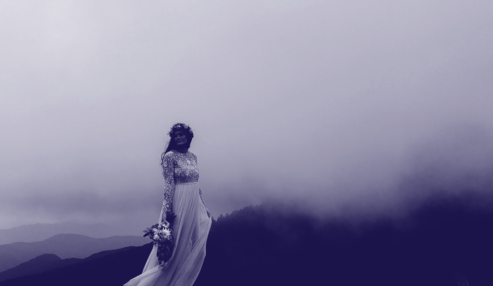 Image of a fair skinned dark haired woman in a white wedding gown standing against a vista of fog capped mountain ridges. The image has a dark purple overlay.