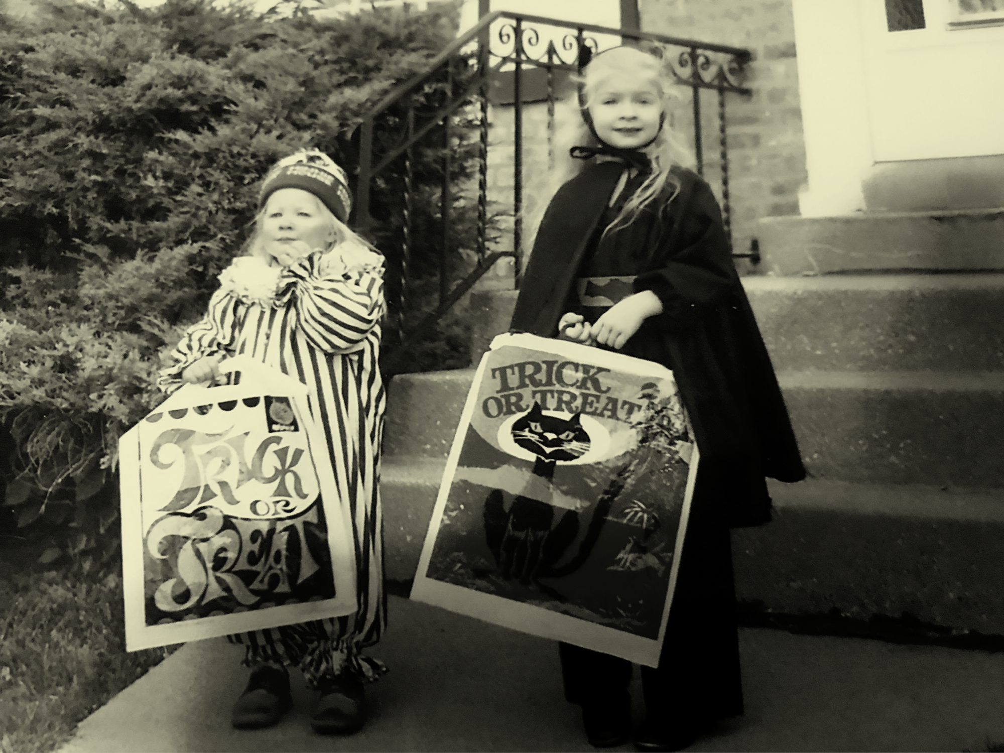 Two blonde and fair skinned children stand outside at the foot of a small cement staircase in homemade halloween costumes (a clown on the left, batgirl on the right), holding square plastic bags printed with halloween/trick-or-treat designs. The taller blonde child on the right (bat girl) is the author. The image has a yellow tint.