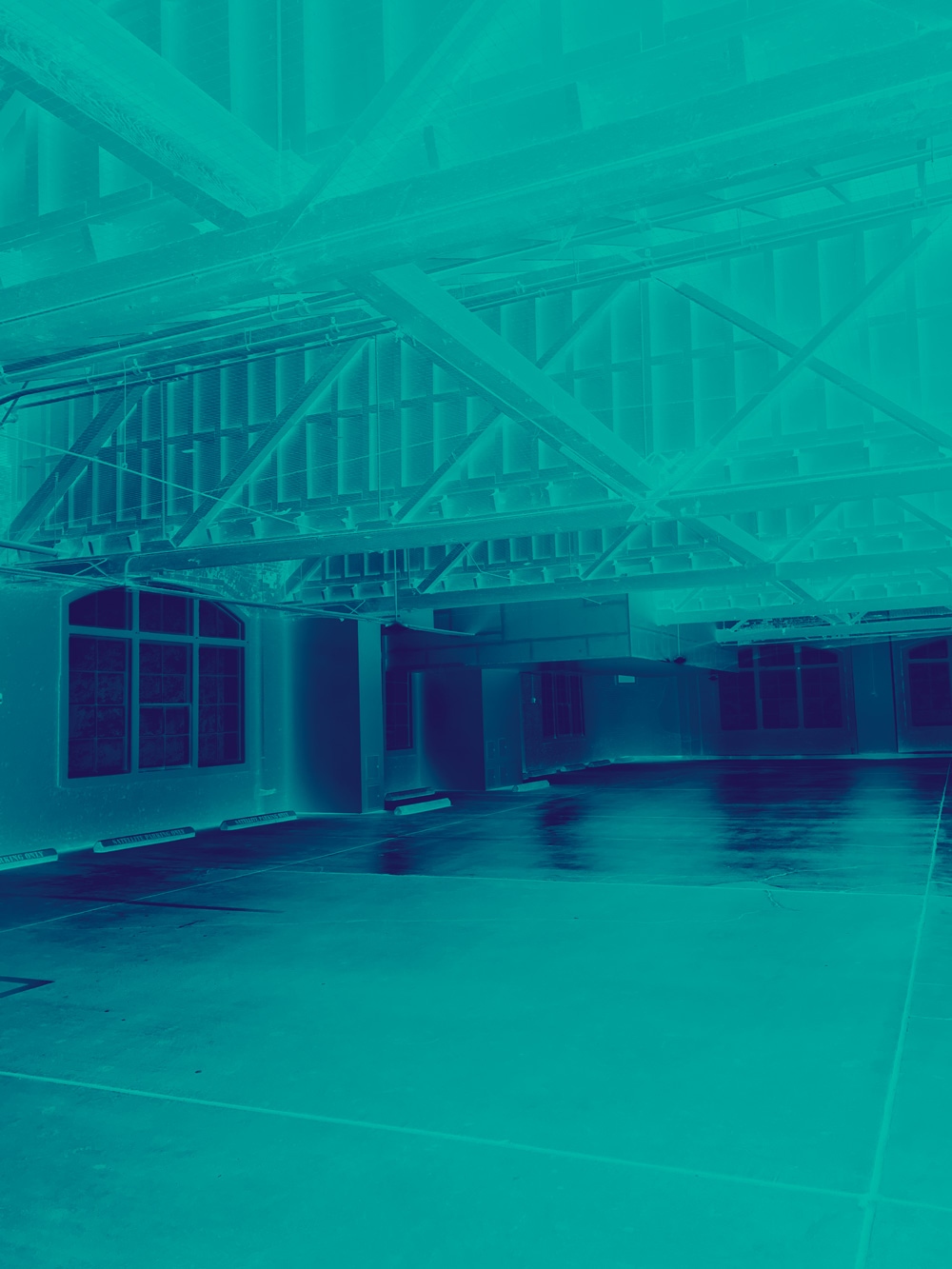 Image of an empty parking garage - there are a lot of steel beams overhead. The image is inverted and tinted in blue and purple