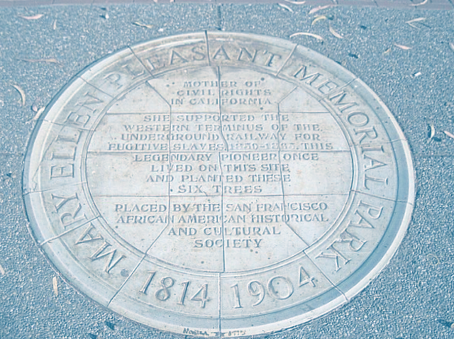 """Photo of a round plaque embedded in a sidewalk - the plaque reads """"Mary Ellen Pleasant Memorial Park 1814 - 1904"""" around the outside rim. The inside of the circle reads: """"Mother of civil rights in Californai. She supported the western terminus of the underground railway for the fugitive slaves 1850-1865. This legendary pioneer once lived on this site and planted these six trees. Placed by the San Francisco African American Historical and Cultural Society."""""""