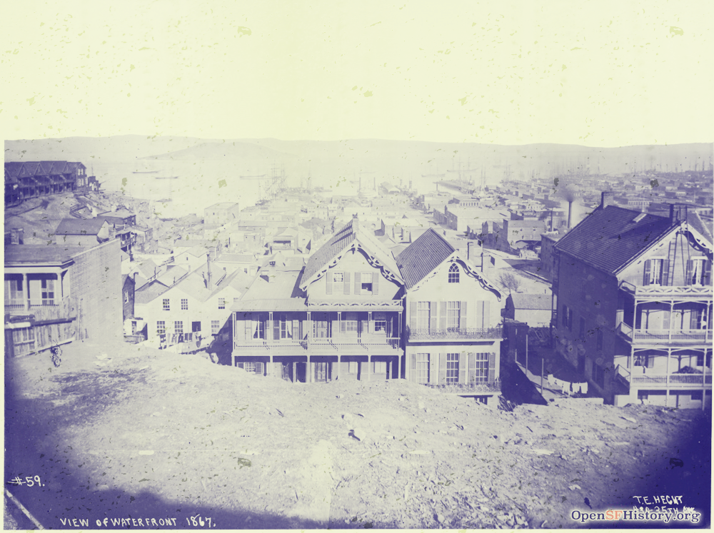Photo of San Francisco in 1867 - the foreground is a barren dirt hill top looking out and down on wooden houses receding into the distance. In the far background you can see small ships floating on San Francisco Bay.s