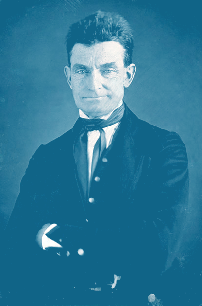 """Portrait of a white man with dark hair cut to about 2-3"""" in length, a dark coat over a white shirt, with a dark scarf knotted at his throat. HIs arms are folded in front of him and he is wearing a bit of a knowing smirk."""