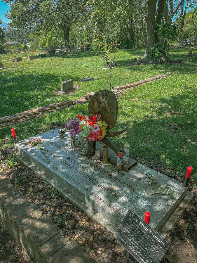 """Photo of a grey stone grave marker with candles and flowers on top. The four corners of the marker have red candles. There are white markings drawn on the grave marker in white chalk or paint that look like a veve for Baron Samedi. The grave marker reads: """"Mary Ellen Pleasant, Mother of Civil Rights in California, 1817-1904, She was a friend of John Brown, San Francisco African American Historical and Cultural Society."""" There is a small sign on fixed to the grave corner that says: """"Mary Ellen Pleasant, who was born a slave, blame known as the 'Mother of Civil Rights in California.' She was involved in the activities of the Underground Railroad in her early adulthood, and was a successful business woman in San Francisco during the Gold Rush era. She was always an advocate for members of the Black community."""""""