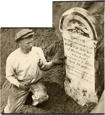 """A black and white photo of steam shovel operator Joseph Bush posing with a gravestone that was uncovered during excavation for the Federal Building in Civic Center, March 6 1933.  He is a fair skinned man in a newsboy style hat, kneeling in the dirt in dusty clothes, holding up a stone grave marker for the camera. The marker says """"Sacred to the memory of Joseph Hicks of Boston MA. [He has] died November 2, 1850. Aged 19 years."""" The rest of the marker is illegible."""