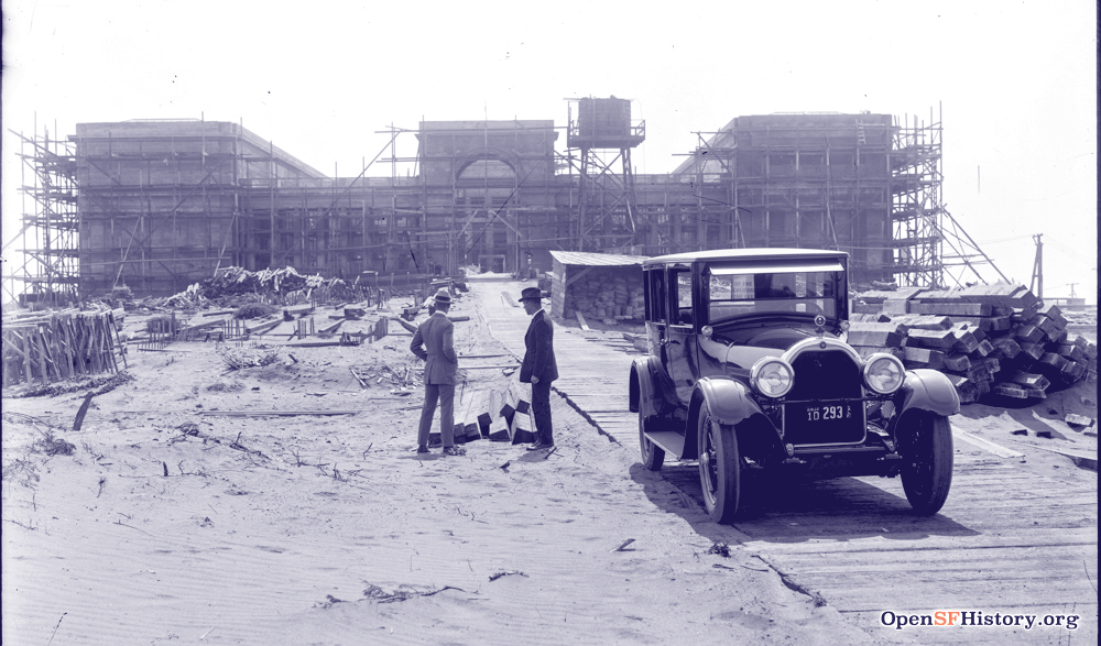 A black and white photo from 1923 of the Legion of Honor museum under construction. The building is in the far distance surrounded by scaffolding. Two men in suits stand in the foreground on bare dirt/sand, looking back at the construction. To the right is an old car on a makeshift path made of wooden planks.
