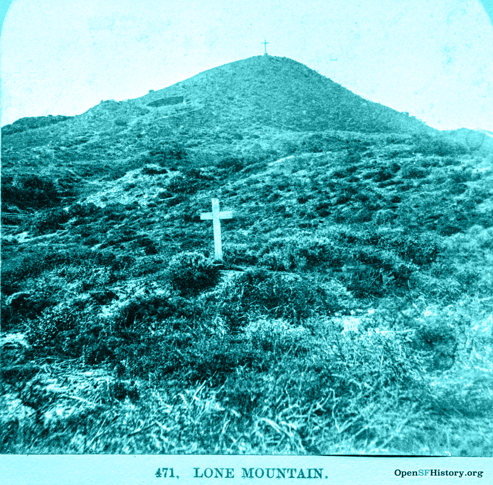 An 1867 photo of Lone Mountain showing a hill sloping upward, covered in low scrub brush. In the foreground is a single white wooden cross. A larger cross can be seen on the summit of the hill in the distance.
