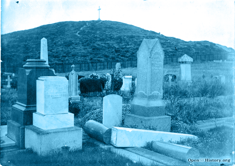 A photo of a graveyard, with some monuments toppled over. Lone Mountain and its summit cross can be seen in the background .