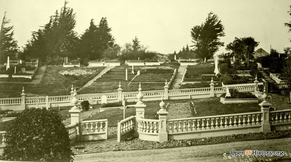 A photo of an orderly cemetery on a hill. Areas are clearly demarcated by elegant stone fencing in good repair. Cypress trees run along the hill top. There are tidy gravel paths throughout.