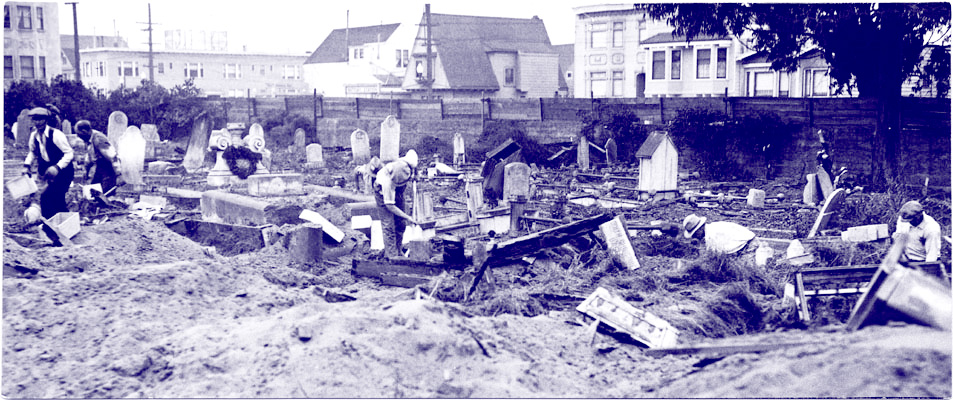 A photo of many workers waist deep in the dirt excavating graves. The ground is covered in mounds of dirt, pieces of wooden paneling, and leaning grave markers. It is a chaotic scene.
