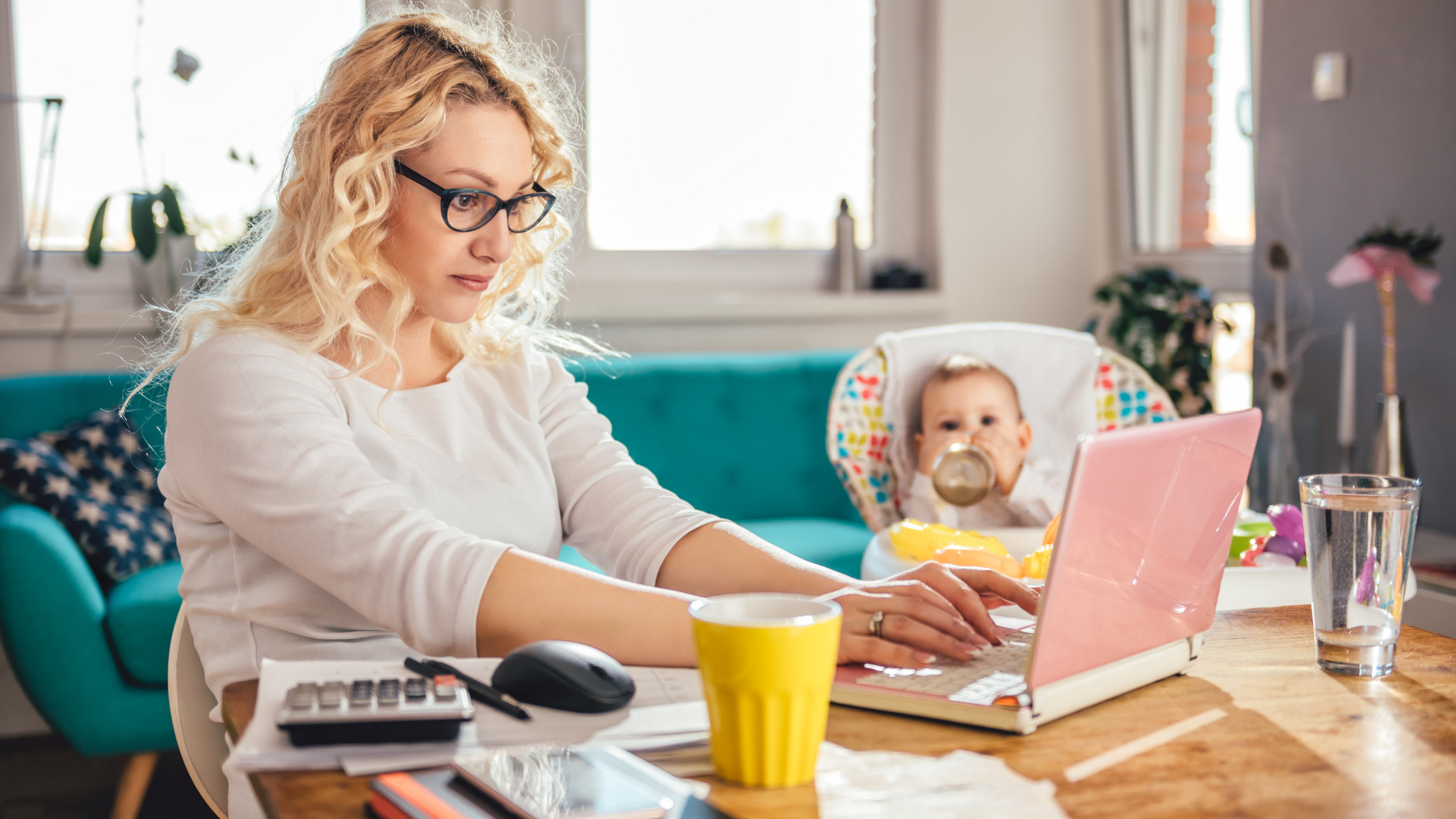Image of woman working on kitchen table with baby in high chair.