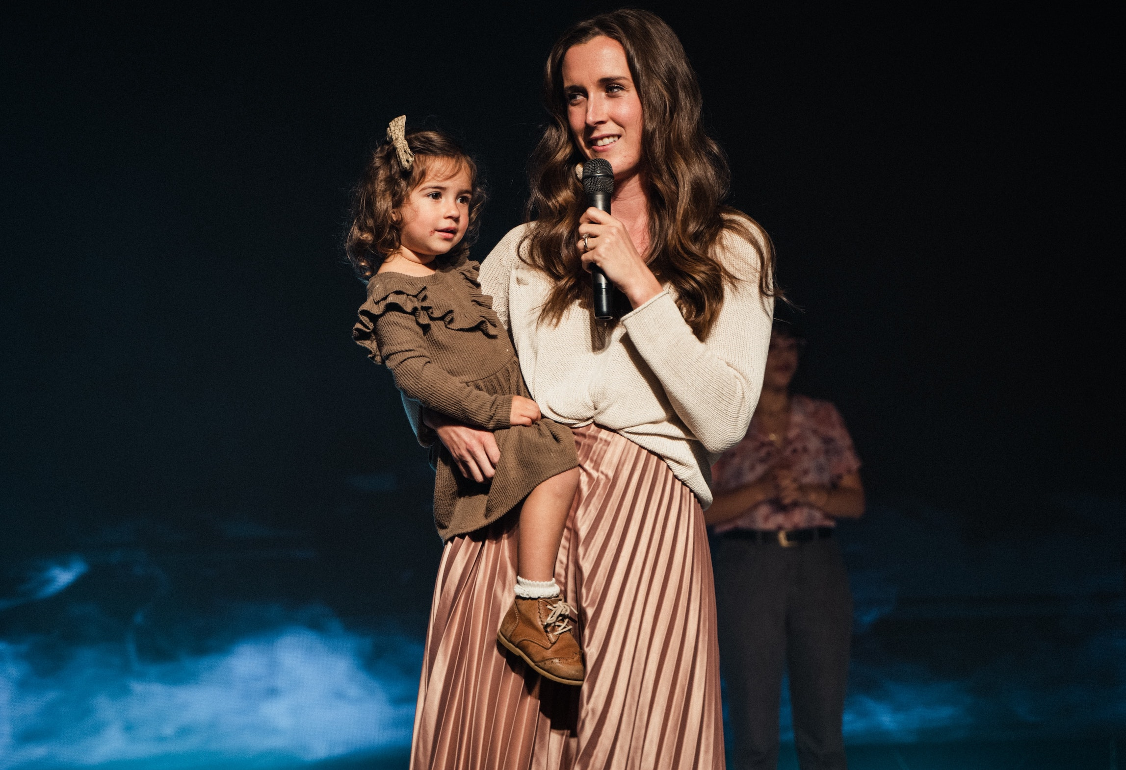 Woman with girl toddler on her hip talking into a microphone