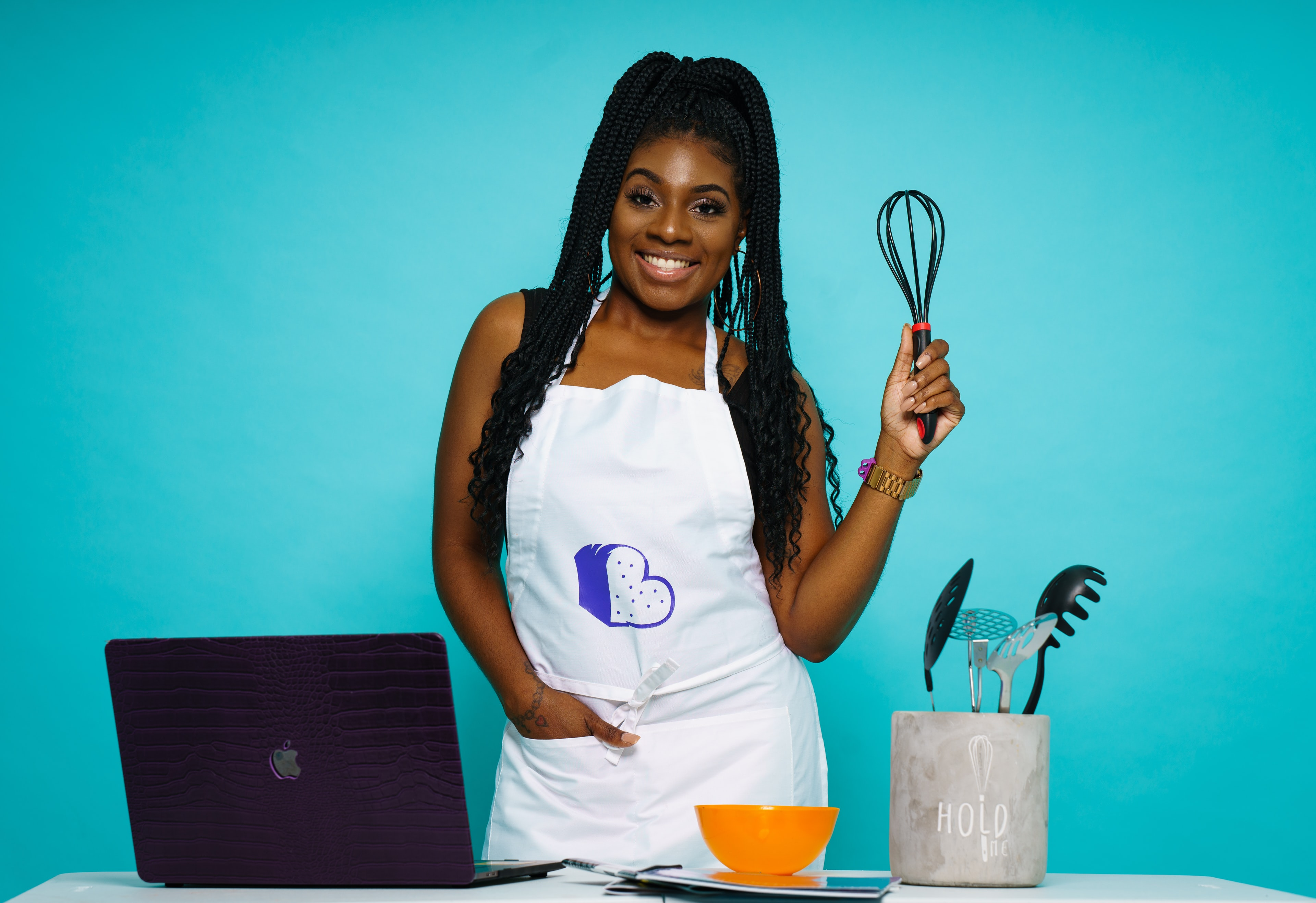 Woman wearing an apron, holding a whisk in front of a blue background