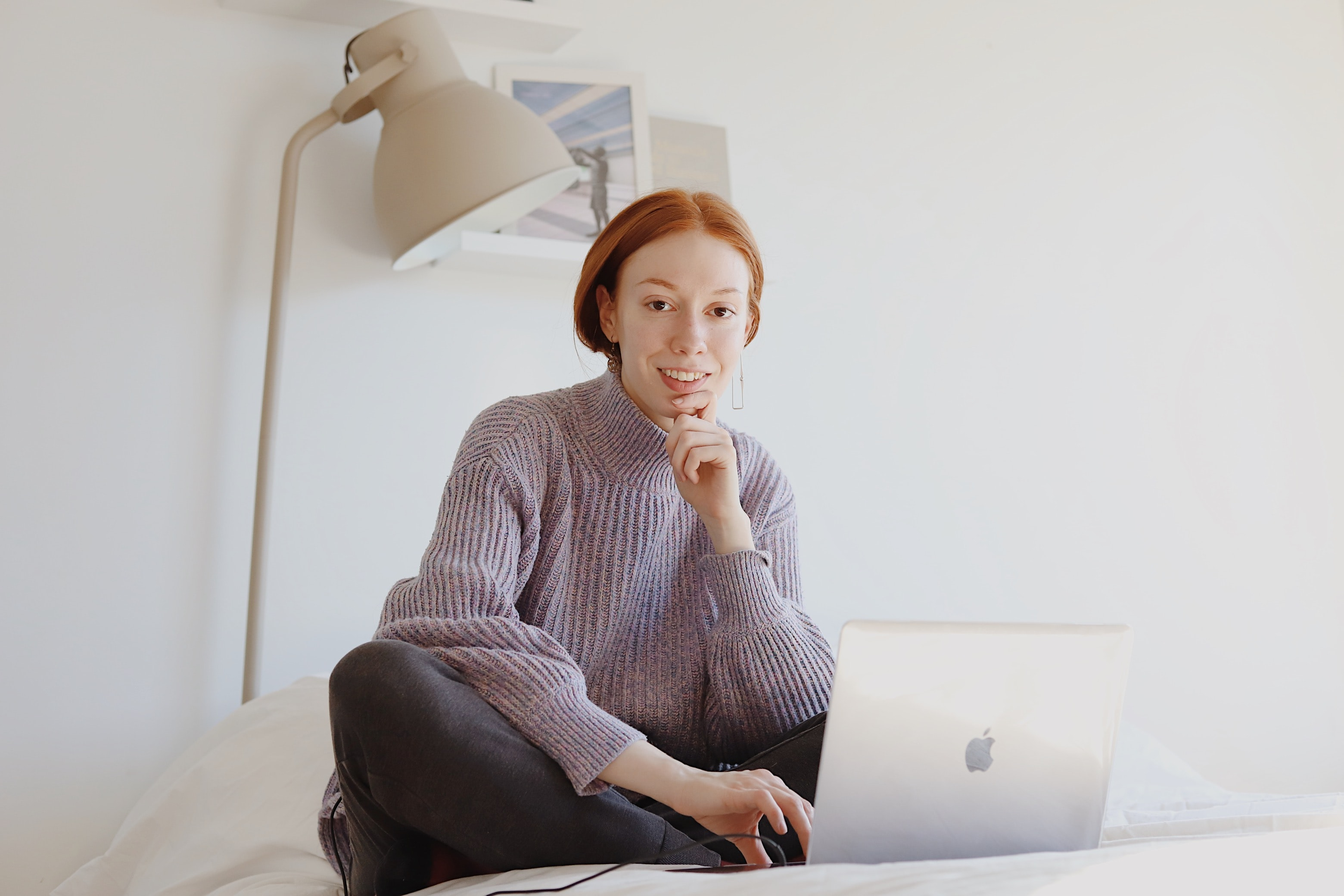 Image of woman sitting on a white bed with a laptop