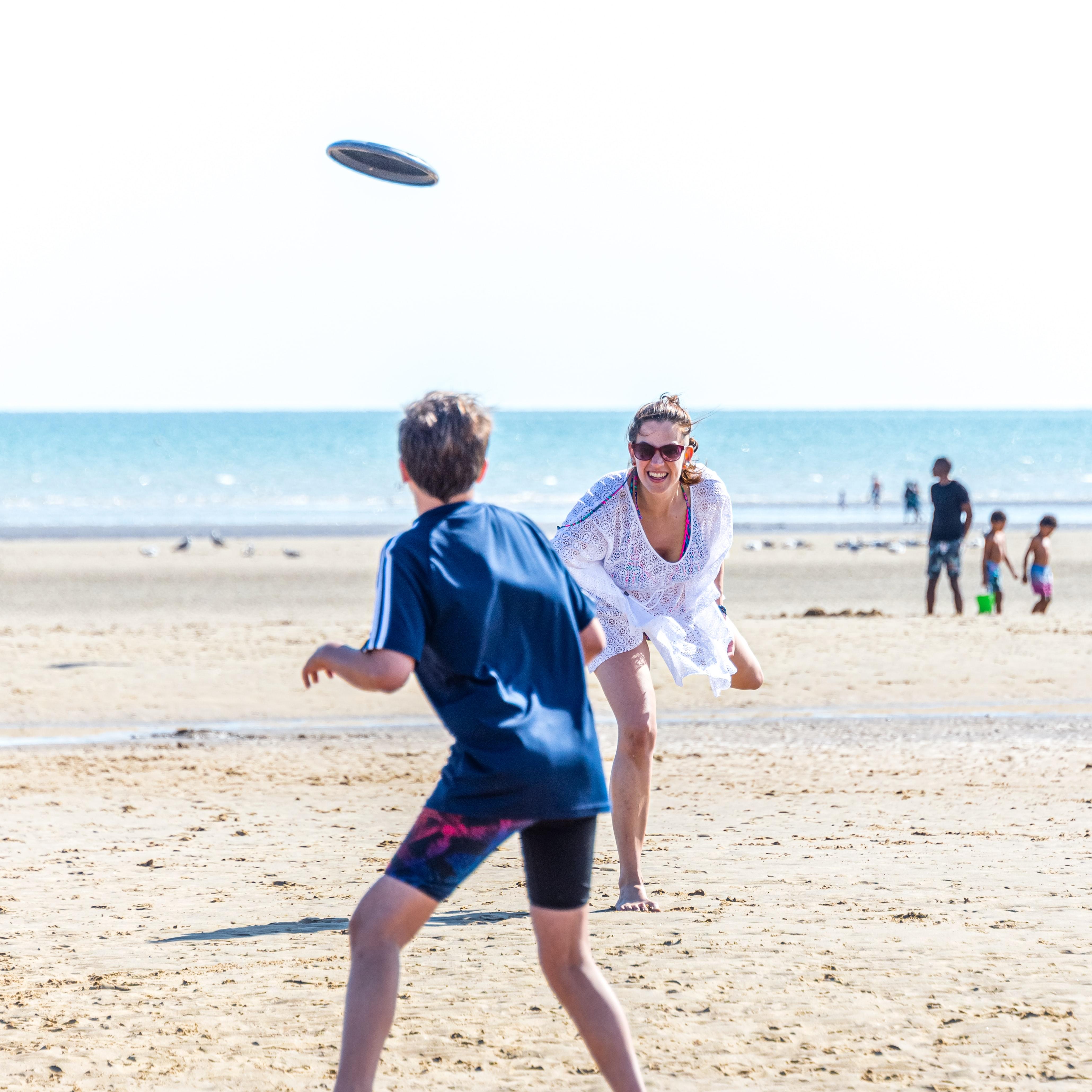 Woman plays frisbee on beach with teenage boy