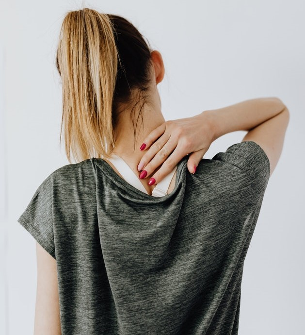 A woman viewed from behind rubbing her neck in discomfort or soreness