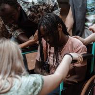 FFM staff praying for a woman in a wheel chair