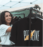 Girl smiling and picking out shirts