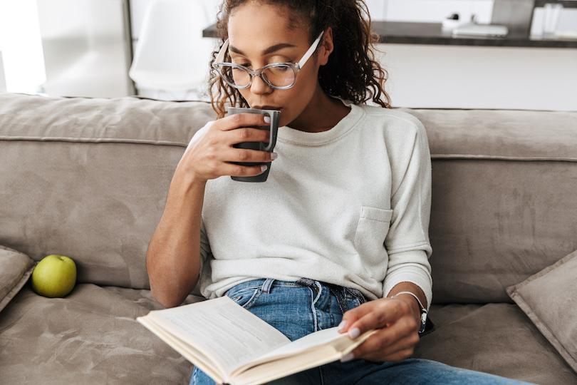Frau mit Kaffeetasse und Buch auf dem Sofa