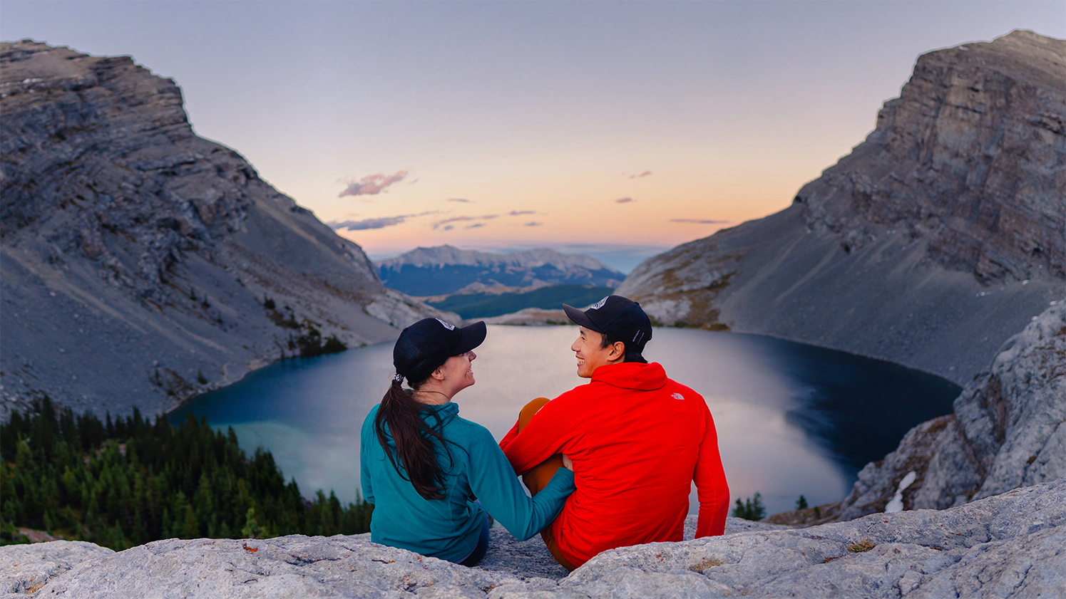 Man in red fleece and woman with ponytail in green fleece sit in front of carnarvon lake in kananaskis country at sunset