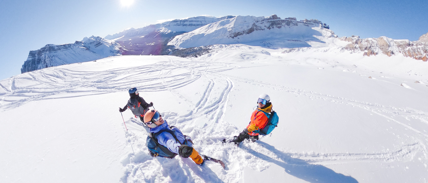 Backcountry skiier and splitboarders ski touring oxo puzzle peak ramp along the icefields parkway in banff national park