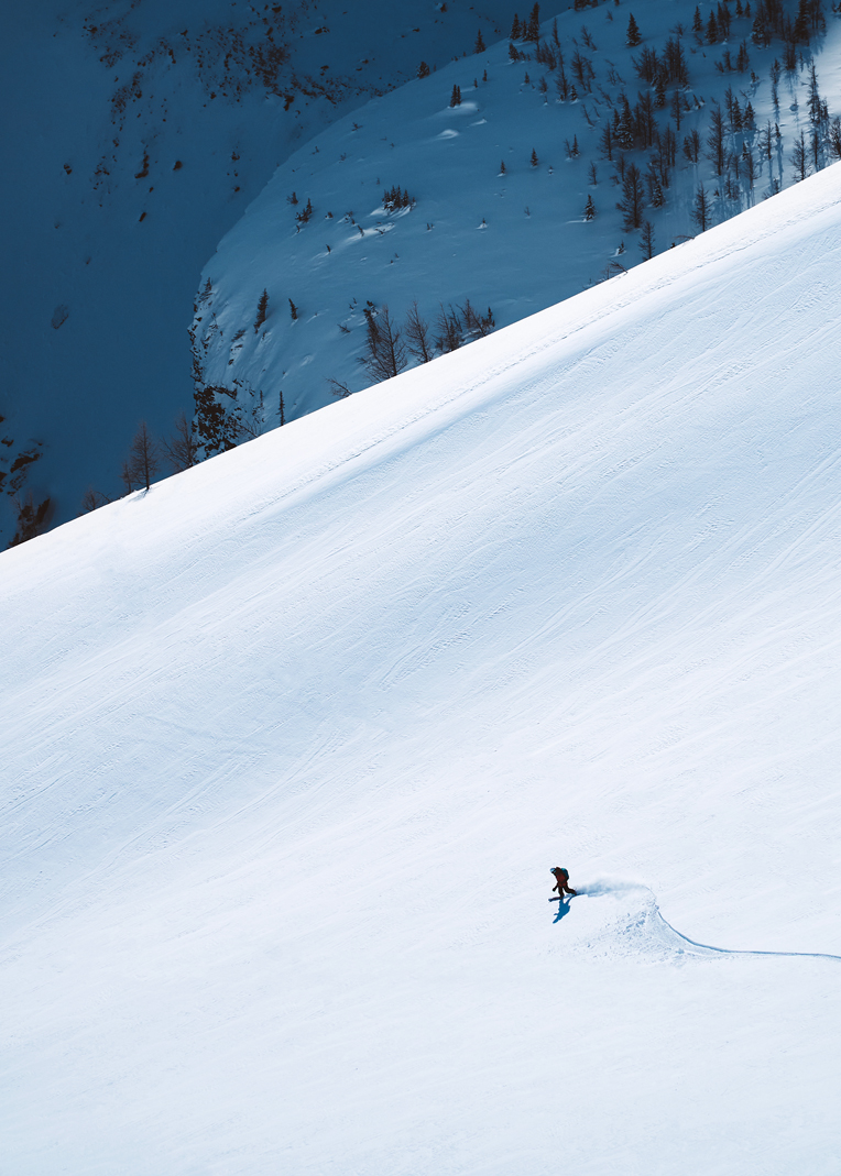 backcountry snowboarder descending a wide powder bowl behind fairview mountain