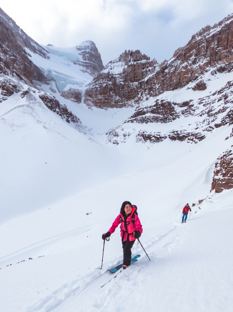 backcountry skiier in pink jacket looking up surprise pass with aberdeen glacier in the background