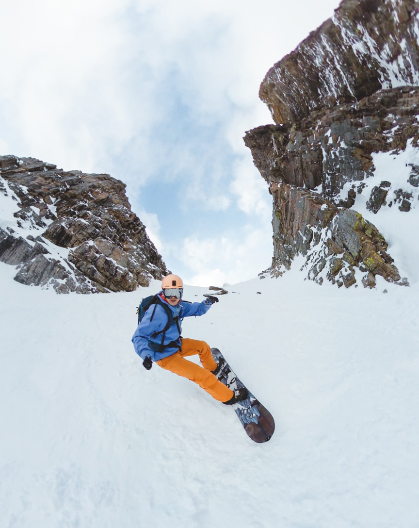 backcountry snowboarder descending surprise pass couloir with rock faces on either side