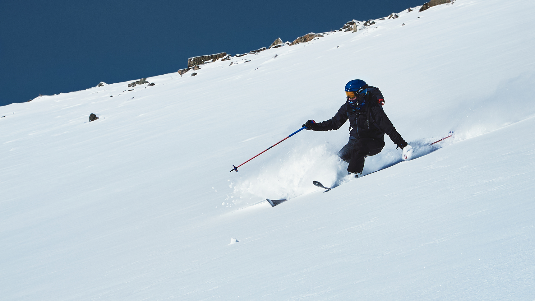backcountry skiier making an aggressive turn in knee deep powder