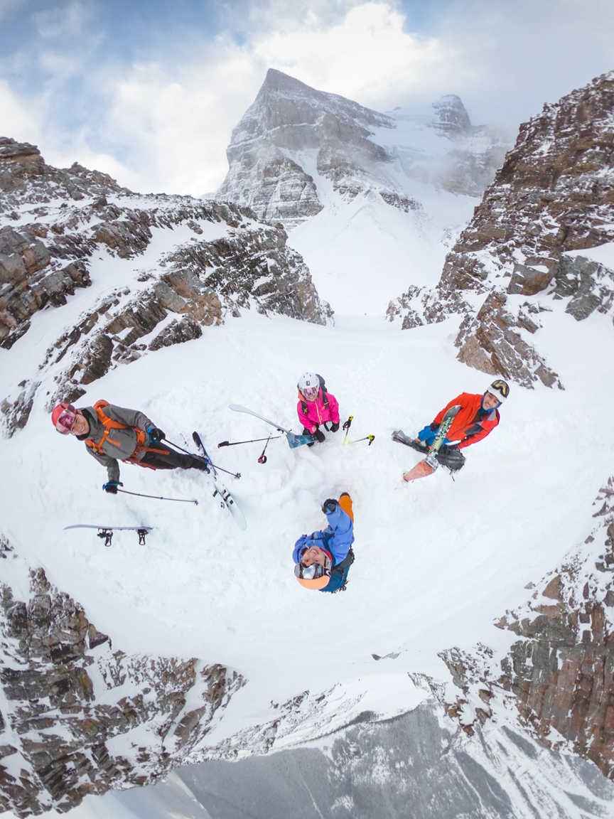 4 backcountry skiiers standing on top of surprise pass couloir