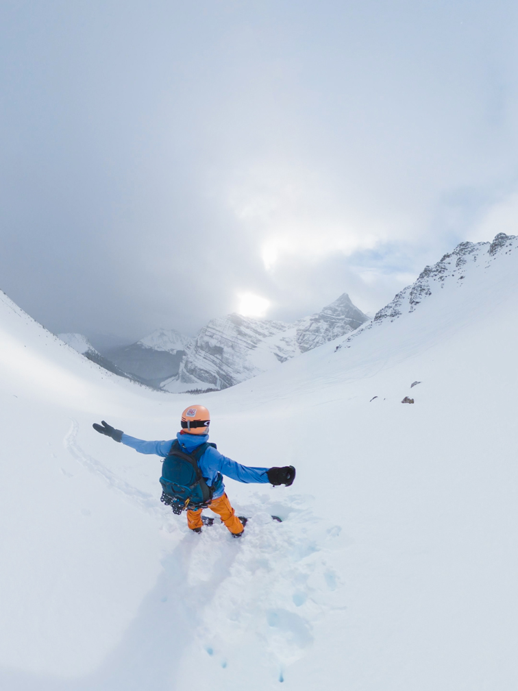 backcountry snowboarder looking down fairview bowl with arms spread wide