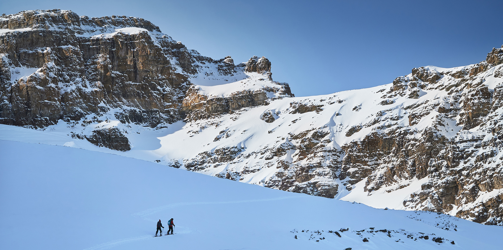 two backcountry skiiers touring through sheol valley towards surprise pass in lake louise