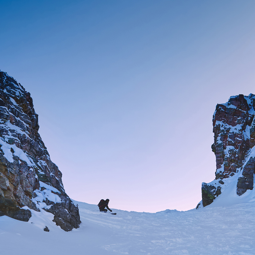 backcountry skiier descending surprise pass with 2 rock faces on either side