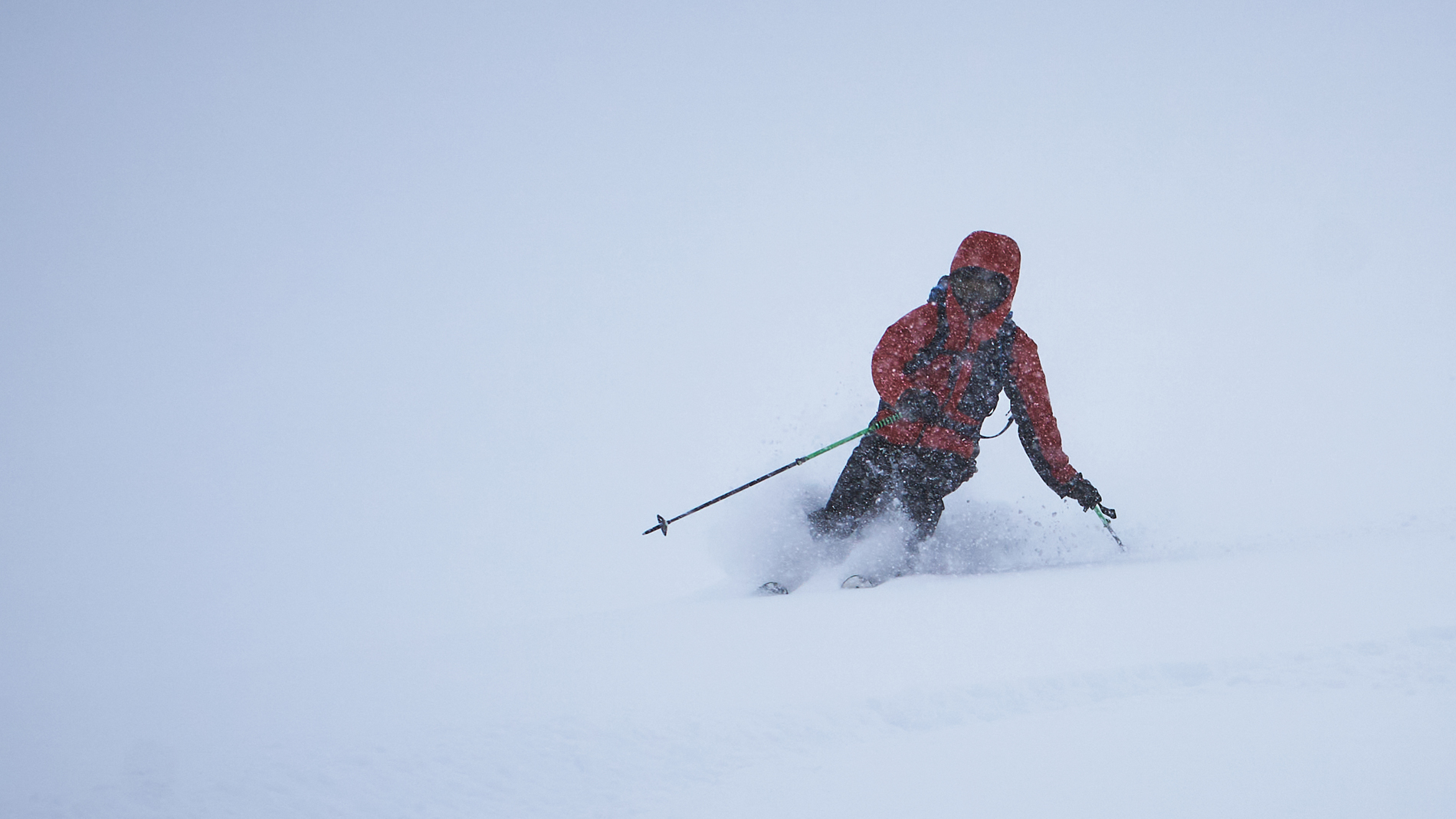 backcountry skiier with red jacket in white out powder