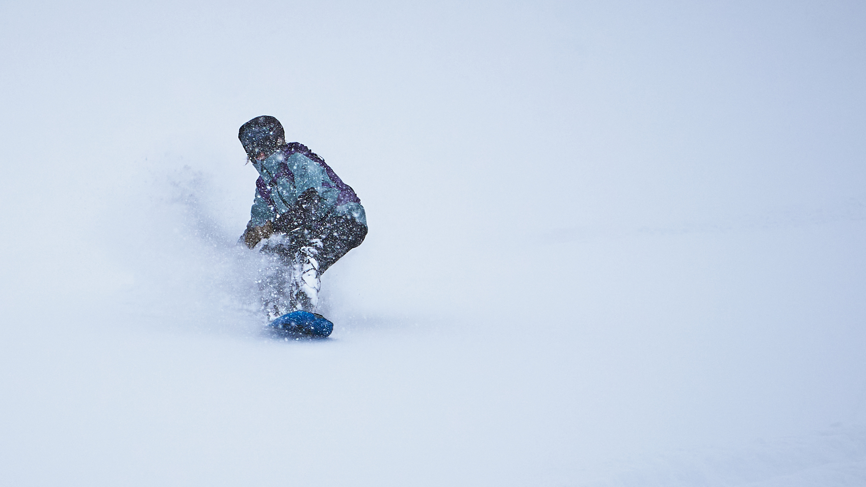 Backcountry snowboarder in green jacket riding deep powder
