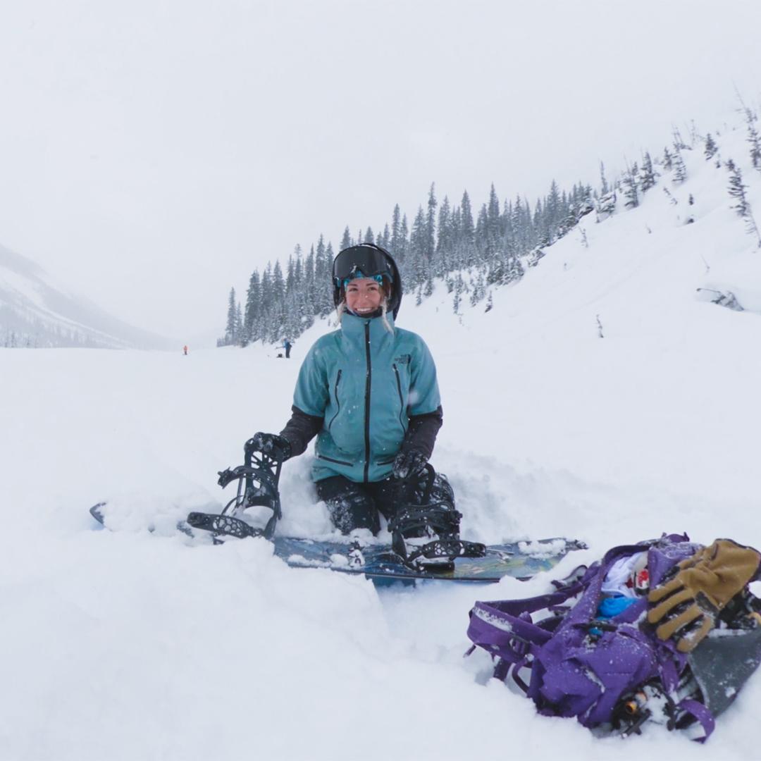 Female backcountry splitboarder transitioning to ski mode