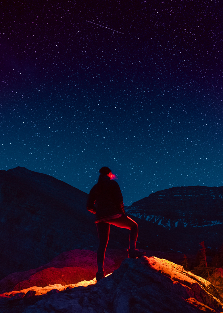 girl standing below milky way with red rocks illuminated by head lamp