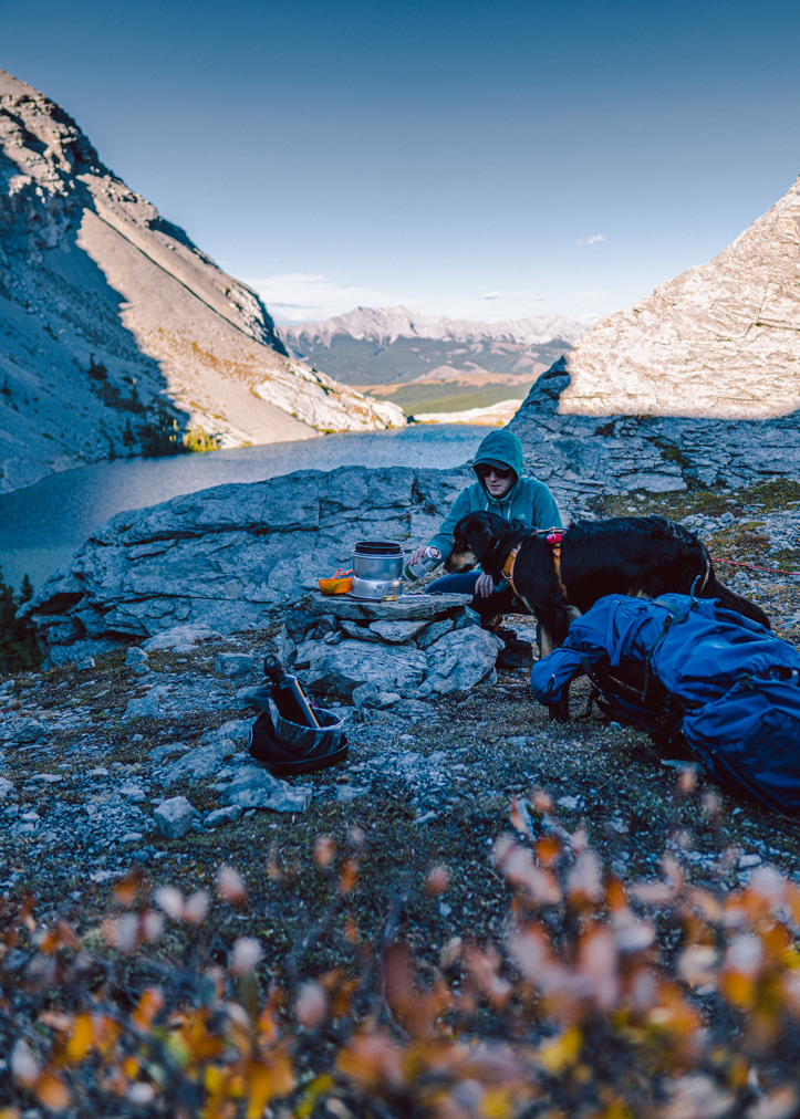 Backcountry hiker and dog preparing dinner with Trangia Stove at Carnarvon lake