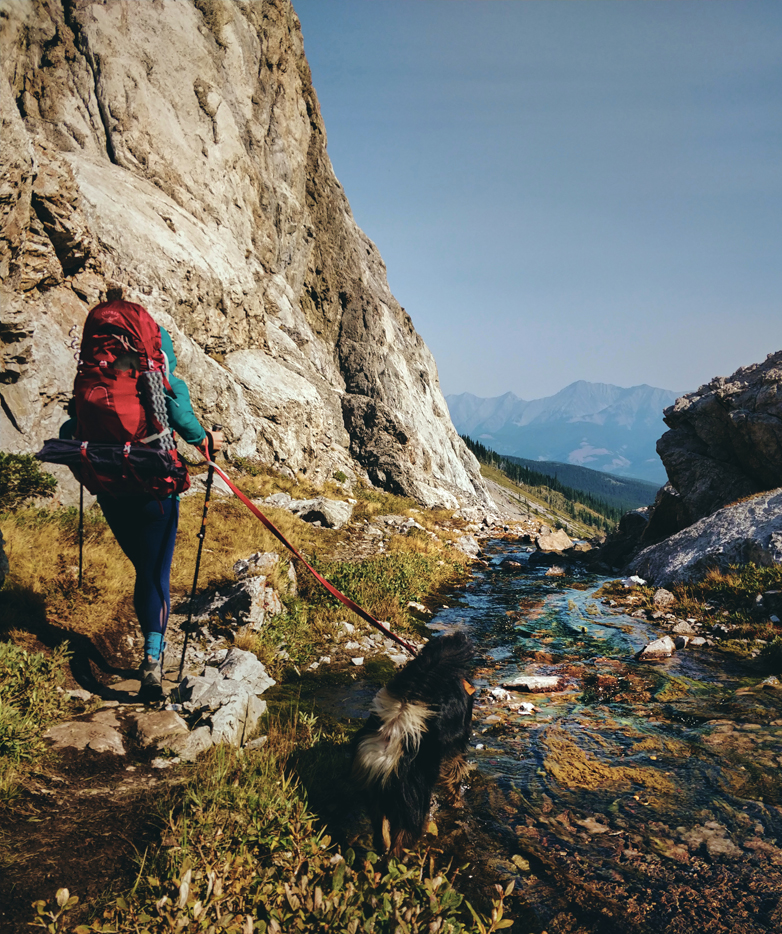 hiker with red osprey aura backpack and black dog walking past water in kananaskis