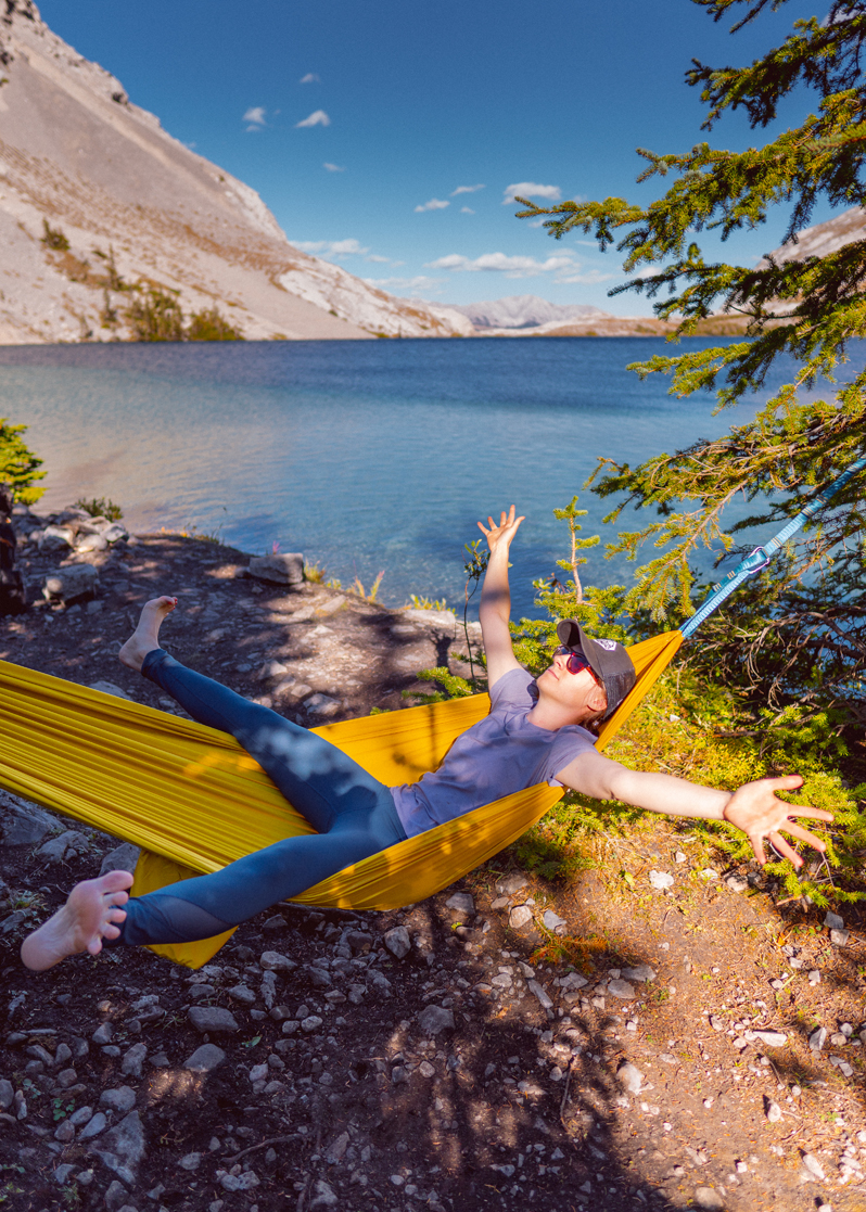 Backcountry camping woman on a yellow hammock