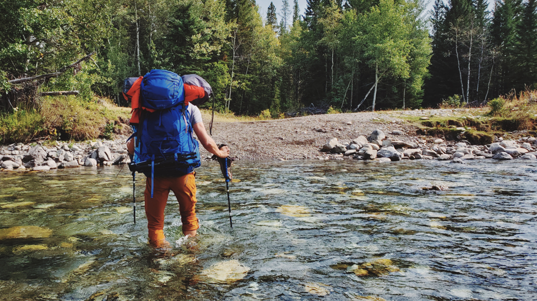 Backcountry camper with blue Osprey Aether backpack crossing river in kananaskis