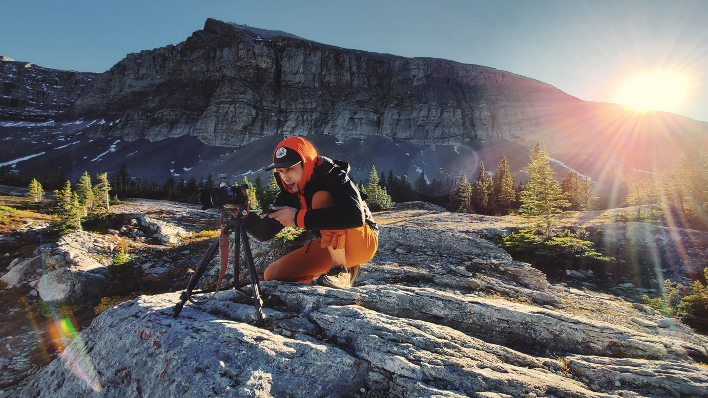 Photographer using tripod in front of sunflare and mountain