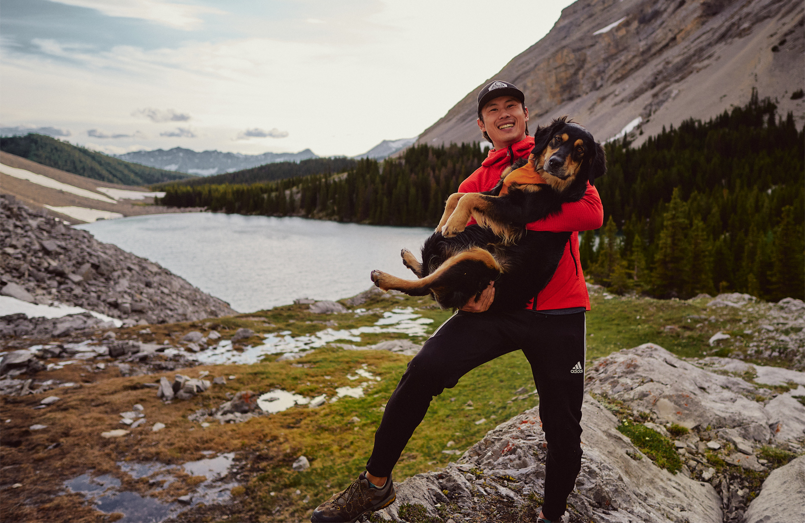 man in red fleece holding black dog in front of pickle jar lakes kananaskis