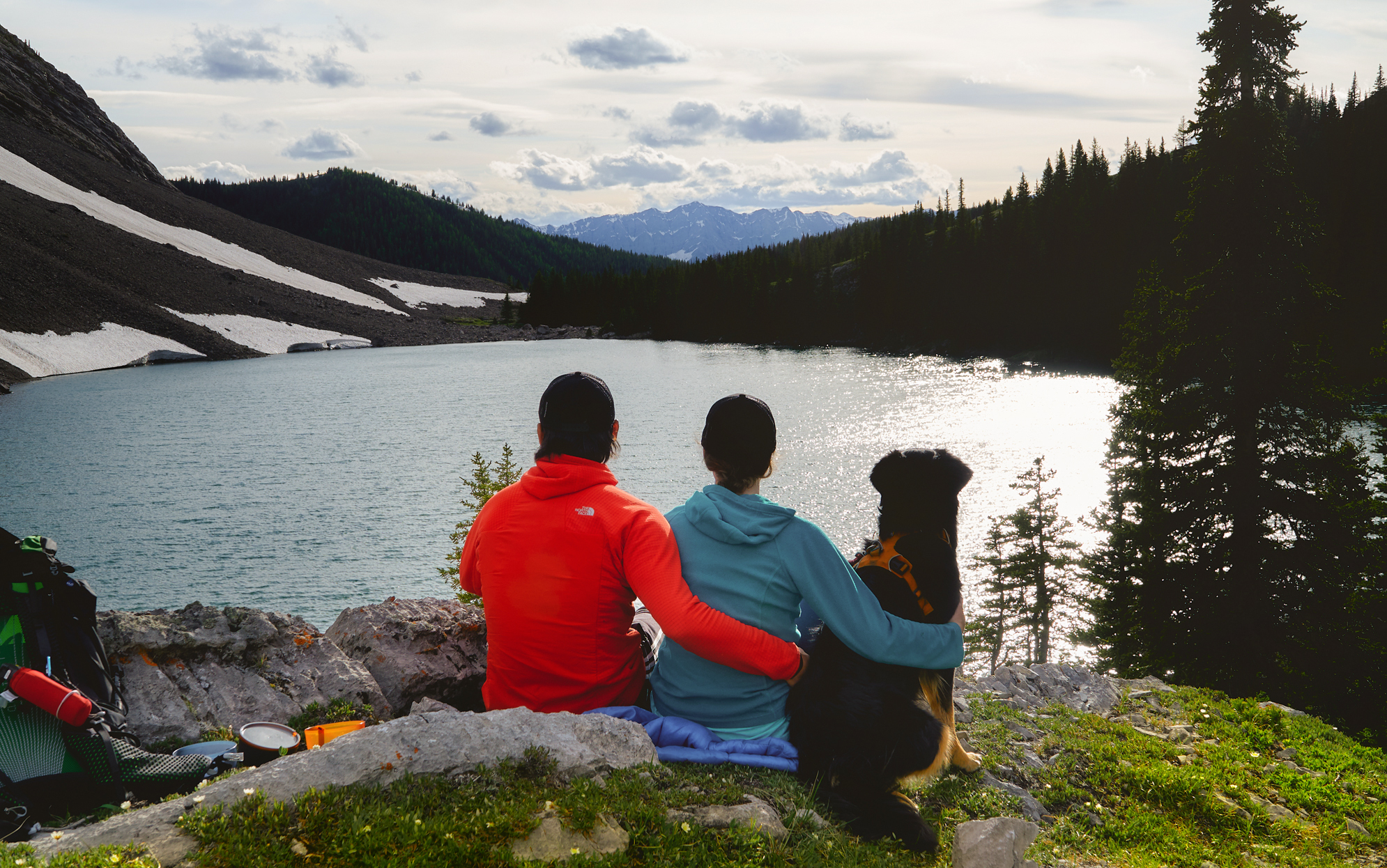 Two hikers and a black dog sit facing Pickle Jar lakes in the late afternoon in Kananaskis Country