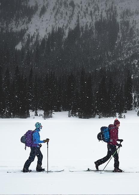 Two backcountry skiiers walking across sherbrooke lake with heavy snow