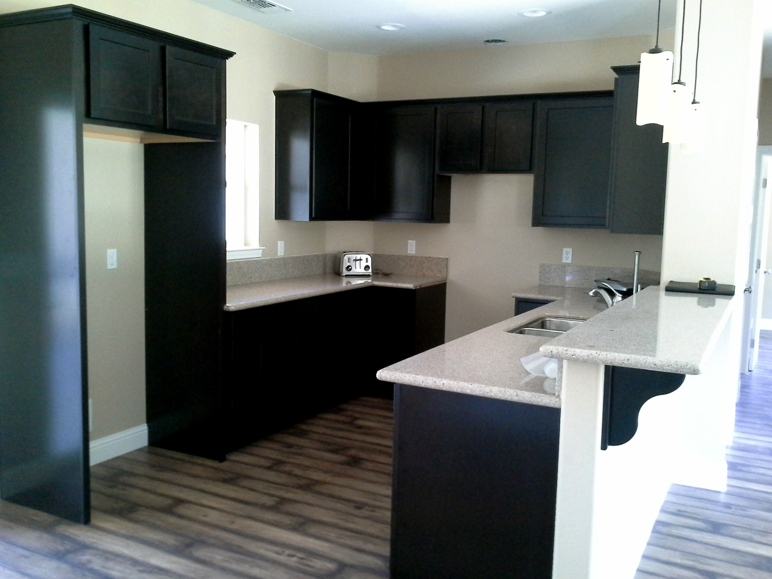 Contemporary kitchen with black cabinets and white countertops