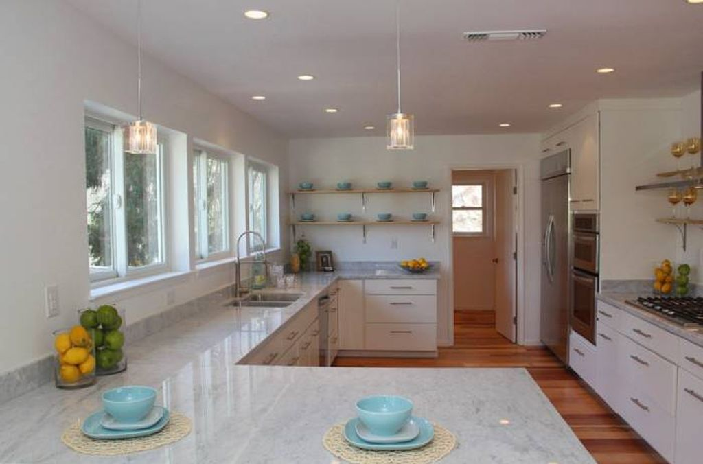 Contemporary kitchen with cream cabinets and white countertops