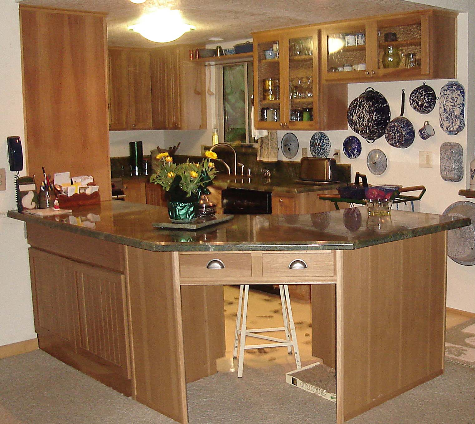 corner counter with maple cabinets and green granite countertop