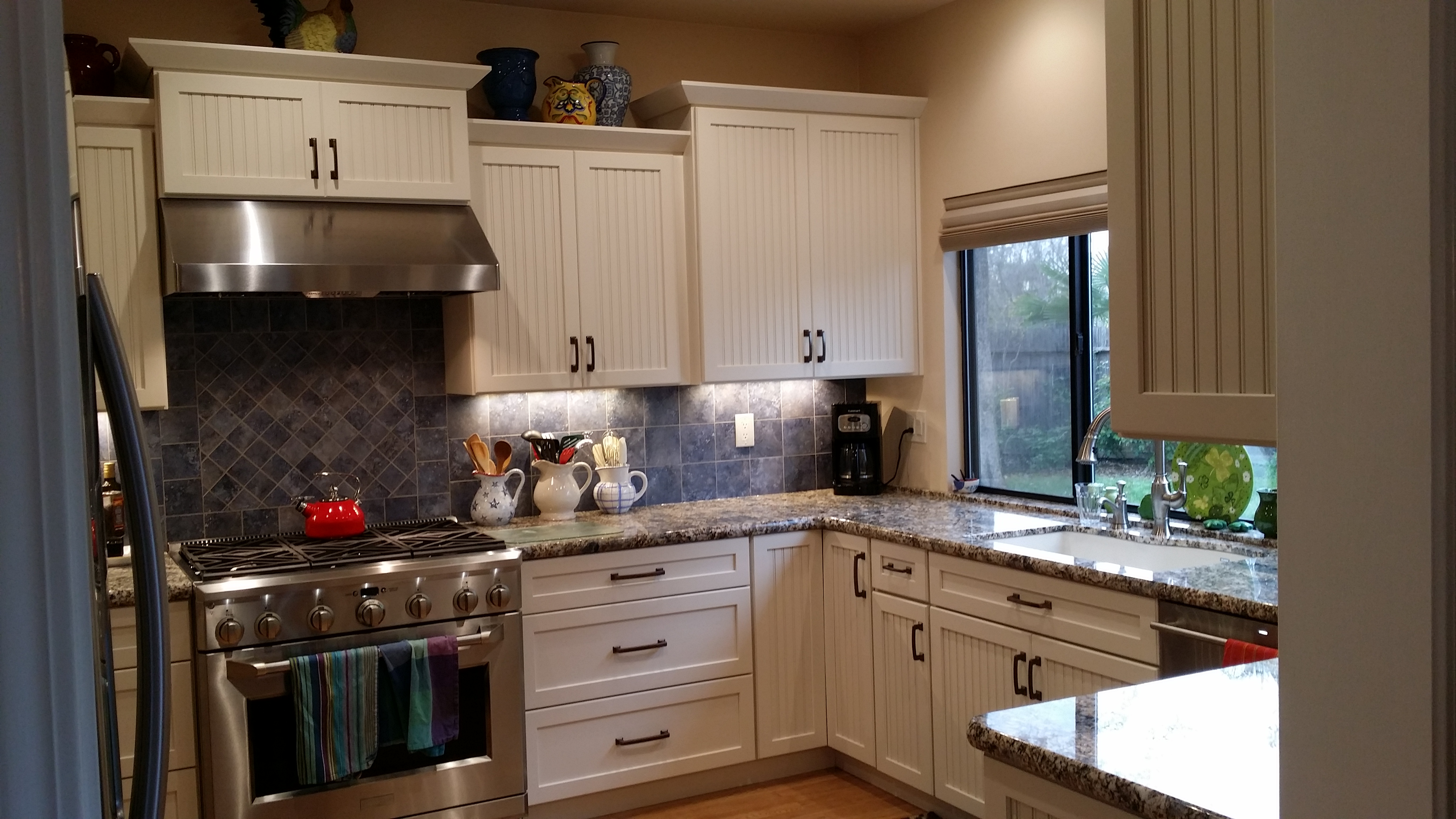 Stainless range and hood surrounded by white cabinets and grey countertop