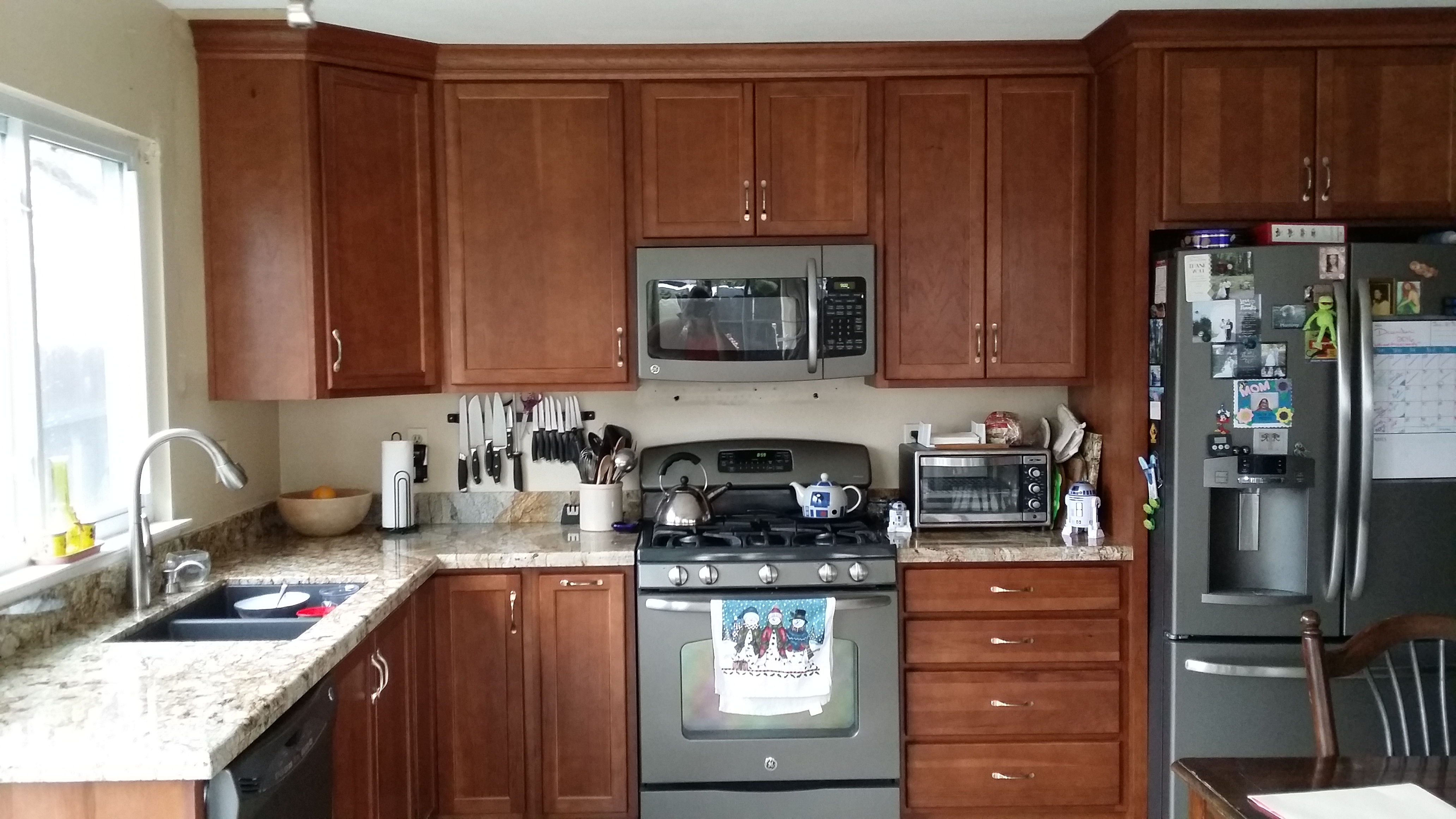 Kitchen sink on white counter with stained cabinets
